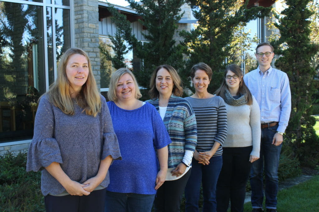 Outreach services department of seven individuals standing and smiling