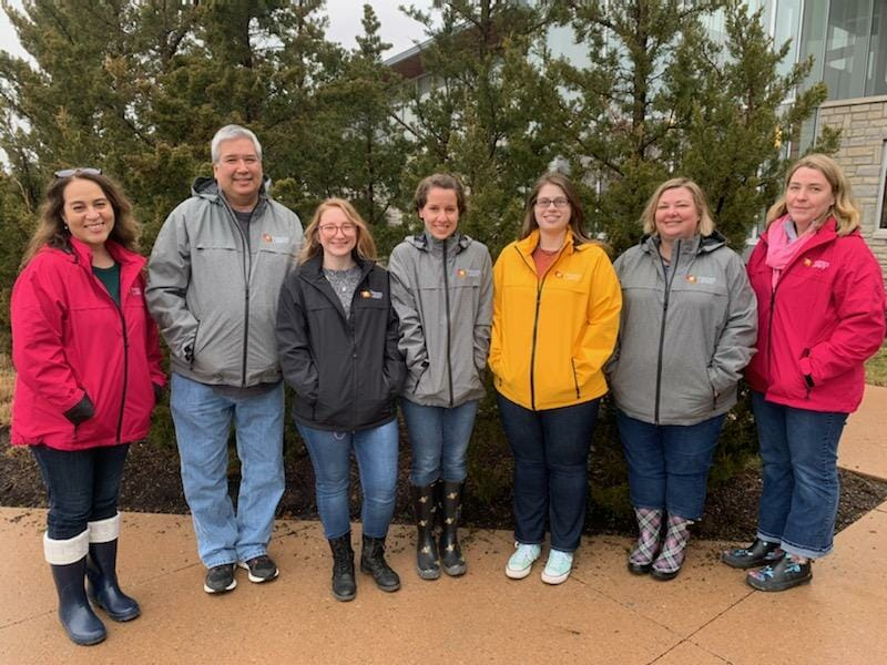 The Outreach Department poses with smiles in their new raincoats.