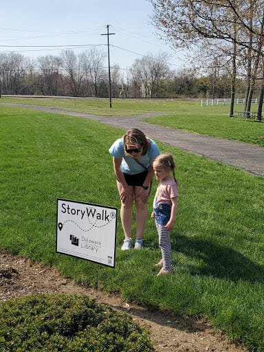 A family reading the storywalk story at the library
